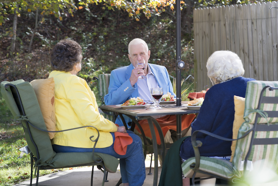 Three Heather Glen at Ardenwoods residents enjoying a meal outside.
